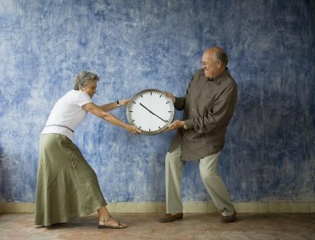 Multi-ethnic senior couple having tug of war with clock Standard-Bild