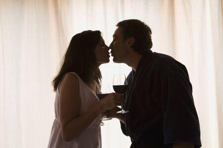 Hispanic couple kissing next to window Stock Photo - 16096170
