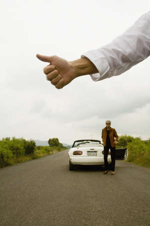 disagreeing: Man holding out thumb for hitchhiking