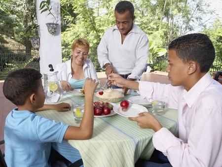 Hispanic family eating pie outdoors Stock Photo - 16096201