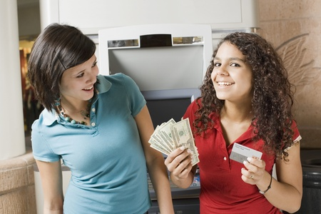 cashpoint: Multi-ethnic teenage girls holding money and credit card