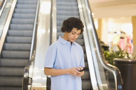 African teenage boy looking at cell phone Stock Photo - 16096226