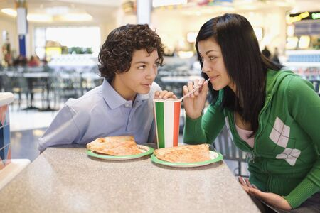Multi-ethnic teenage couple eating at mall Stock Photo