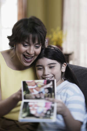 Hispanic mother and daughter looking at photo album Stock Photo - 16096229
