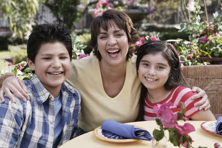 Hispanic mother and children at table Stock Photo - 16096232