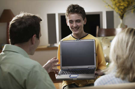 laptop stand: Hispanic boy showing laptop to parents