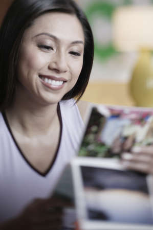 photo album: Asian woman looking at photo album