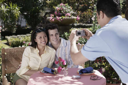 Waiter taking photograph of couple at table Stock Photo - 16096239