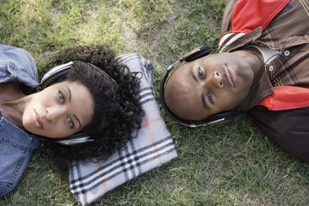 African couple listening to headphones in grass Stock Photo - 16096240