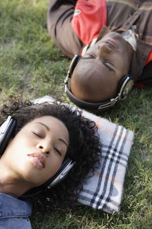 African couple listening to headphones in grass Stock Photo - 16096241