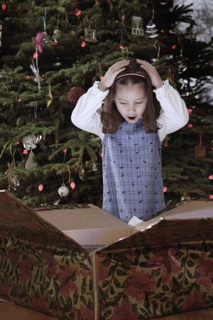 christmas gift: Hispanic girl opening Christmas gift LANG_EVOIMAGES