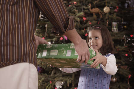fathering: Hispanic father and daughter exchanging Christmas gift LANG_EVOIMAGES