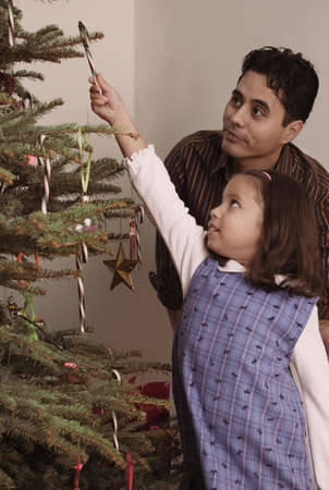 decorating christmas tree: Hispanic girl hanging candy cane on Christmas tree
