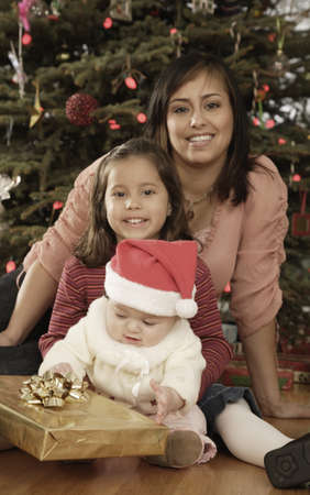Hispanic mother and children in front of Christmas tree Stock Photo - 16096247