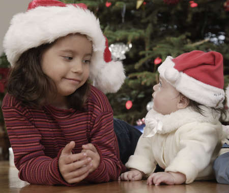 Hispanic girl smiling at baby sibling on Christmas Stock Photo - 16096248