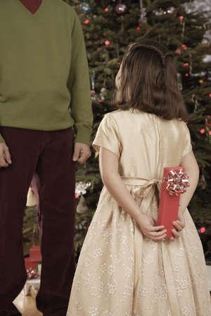 giver: Hispanic girl surprising father with Christmas gift