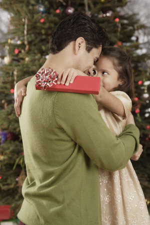 Hispanic father and daughter hugging on Christmas