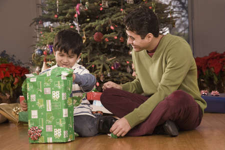 fathering: Hispanic father watching son open Christmas gift