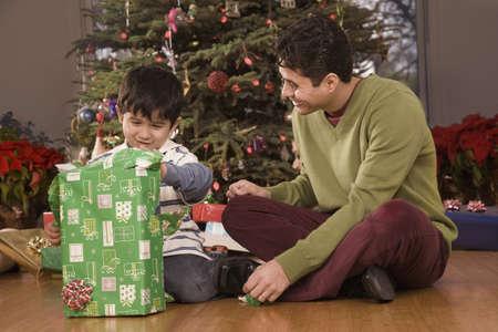 fond of children: Hispanic father watching son open Christmas gift