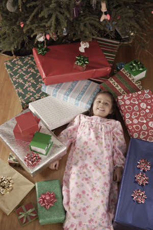 Hispanic girl surrounded by Christmas gifts Stock Photo - 16096254