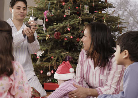 medium group of object: Hispanic father video recording family on Christmas LANG_EVOIMAGES