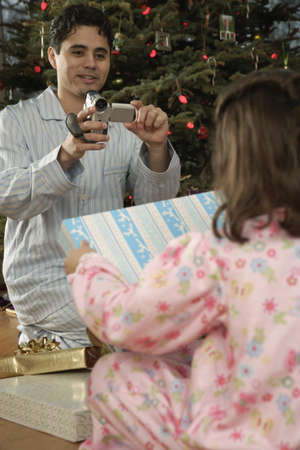 Hispanic father video recording daughter on Christmas Stock Photo - 16096257