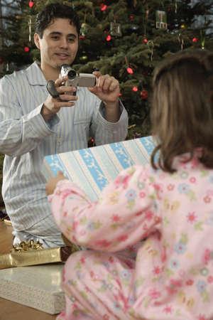 Hispanic father video recording daughter on Christmas Stock Photo - 16096257