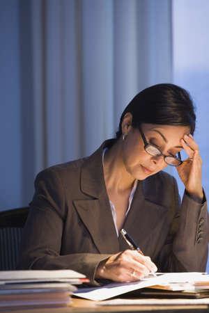 late thirties: Hispanic businesswoman writing at desk LANG_EVOIMAGES