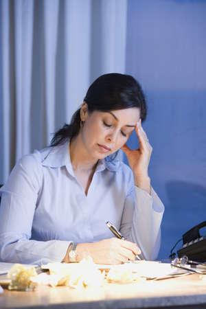 Hispanic businesswoman writing at desk Stock Photo - 16096269