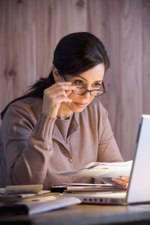 Hispanic businesswoman looking at laptop