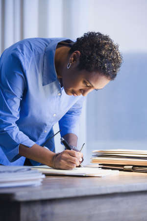 late thirties: African businesswoman writing on paperwork LANG_EVOIMAGES