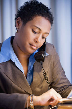 late thirties: African businesswoman checking watch LANG_EVOIMAGES