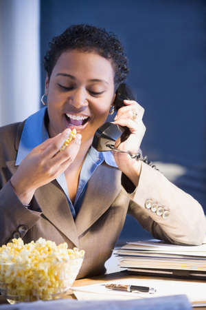 African businesswoman eating popcorn Stock Photo - 16096278