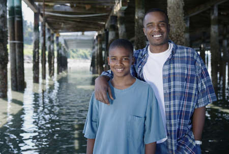 Father and his son standing together under a pier LANG_EVOIMAGES