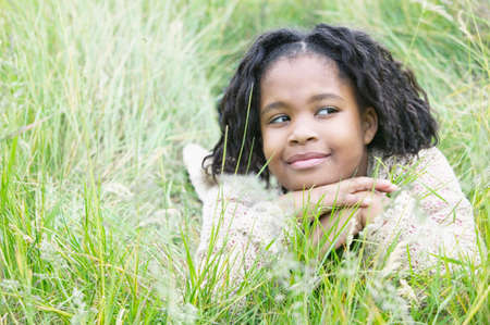 informant: Young girl lying in tall grass smirking