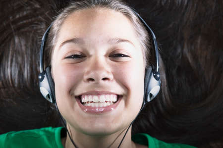 expressional: Portrait of a teenage girl wearing headphones smiling LANG_EVOIMAGES