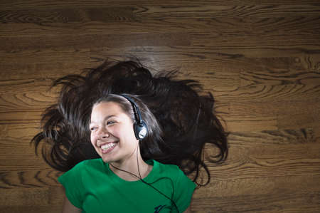 Teenage girl lying on the floor wearing headphone smiling