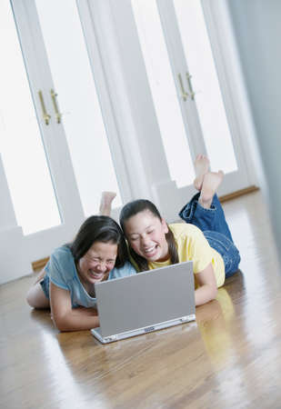 two persons only: Two teenage girls lying on the floor working on a laptop