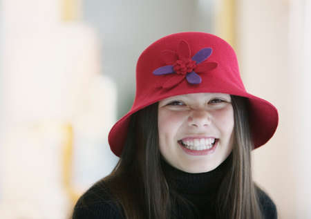 way of behaving: Teenage girl wearing a hat looking at camera smiling LANG_EVOIMAGES