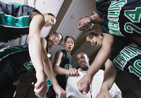 Low angle view of a female basketball team in a huddle on a basketball court