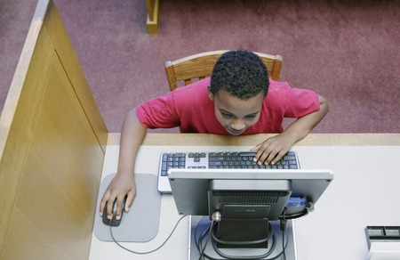 High angle view of a young boy operating a computer at the library