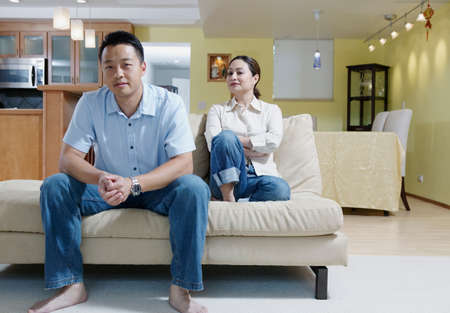 Portrait of a man and a woman sitting on a couch in a house LANG_EVOIMAGES