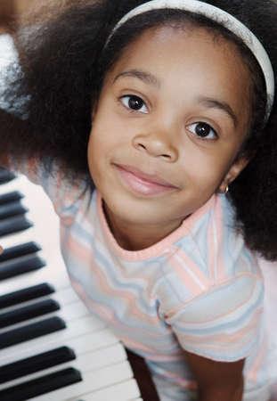 knees bent: Ritratto di una giovane ragazza seduta al pianoforte guardando fotocamera