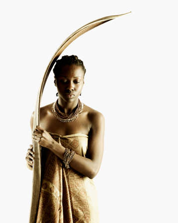 airs: Young tribal woman standing holding a wooden stick