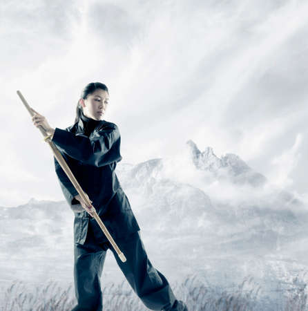 adventurers: Portrait of a young woman holding a wooden stick standing in a martial arts stance