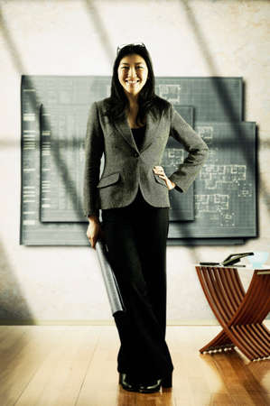 way of behaving: Portrait of a young businesswoman standing in a room looking at camera
