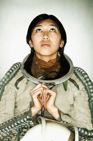invariable: Young female astronaut looking up LANG_EVOIMAGES