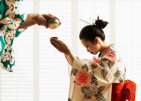 being the case: Side profile of a young woman wearing a kimono being served tea