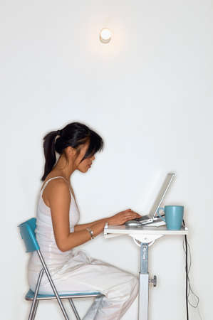 Side profile of a young woman operating a laptop
