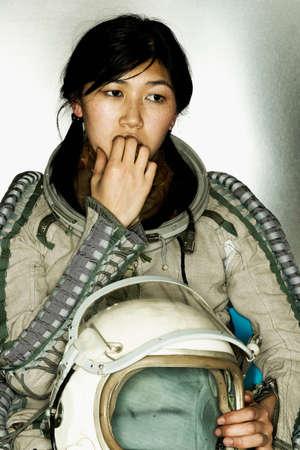 Female astronaut holding a helmet biting her finger nails Stock Photo